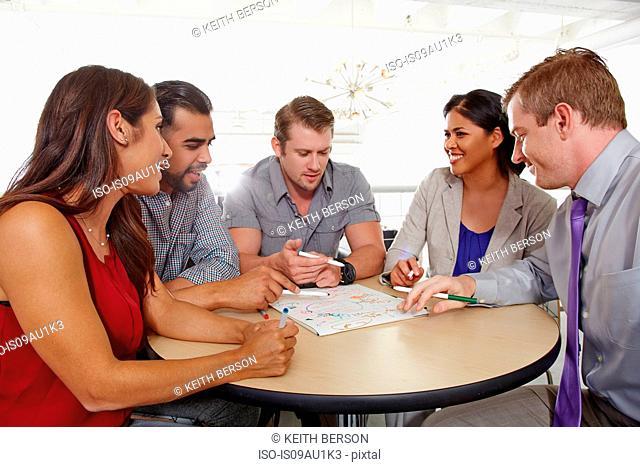 Small group of people having brainstorming business meeting