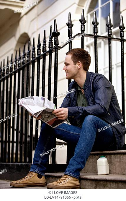 A young man sitting on a step, reading a newspaper