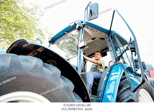 Low angle view of young male farmworker driving tractor