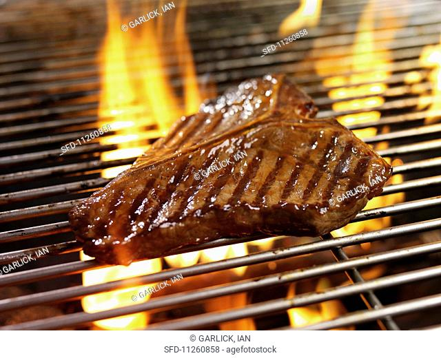 A T-bone steak on a barbecue