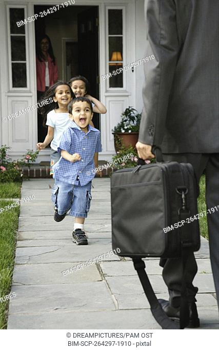 Indian children greeting father in front of house