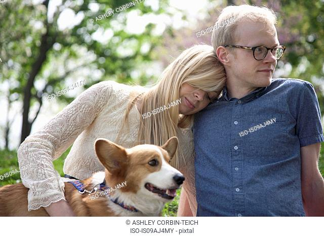 Young couple sitting in park with corgi dog