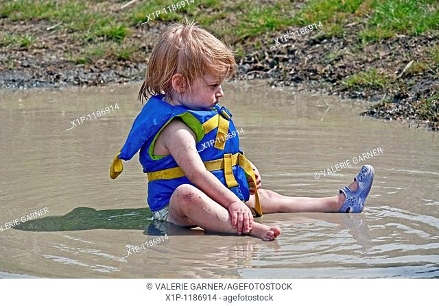 This little toddler girl is wearing a blue life vest and sitting in a mud puddle with a serious expression on her face She's in her diaper also and has one...