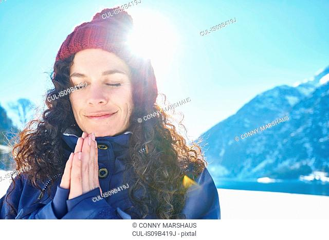 Portrait of woman in knit hat practicing yoga, meditating in snow covered sunlit landscape, Austria