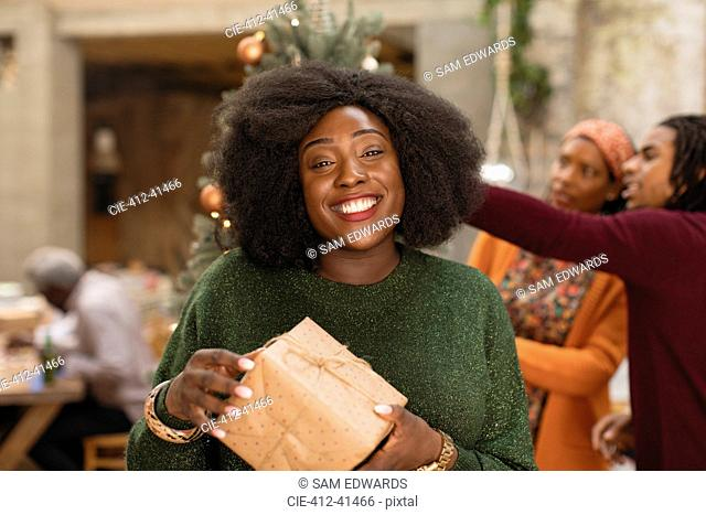 Portrait smiling, confident young woman holding Christmas gift