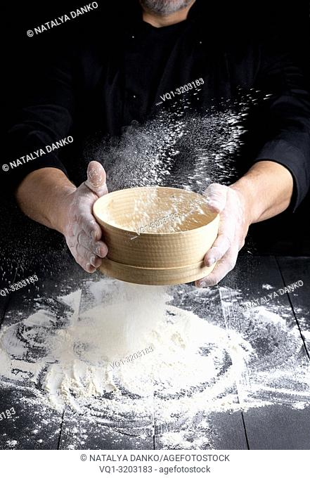 round wooden sieve with flour in male hands, the chef sifts white wheat flour on a black wooden table