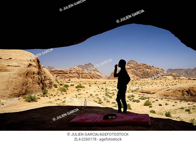 Silhouette of a woman drinking water on a picnic in the desert. Jordan, Wadi Rum desert, protected area inscribed on UNESCO World Heritage list