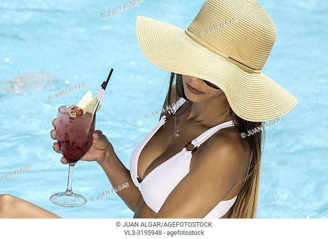 From above of anonymous woman in white bikini and straw hat sitting on poolside with turquoise water holding cocktail