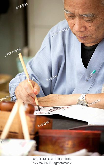 Old man drawing Japanese characters