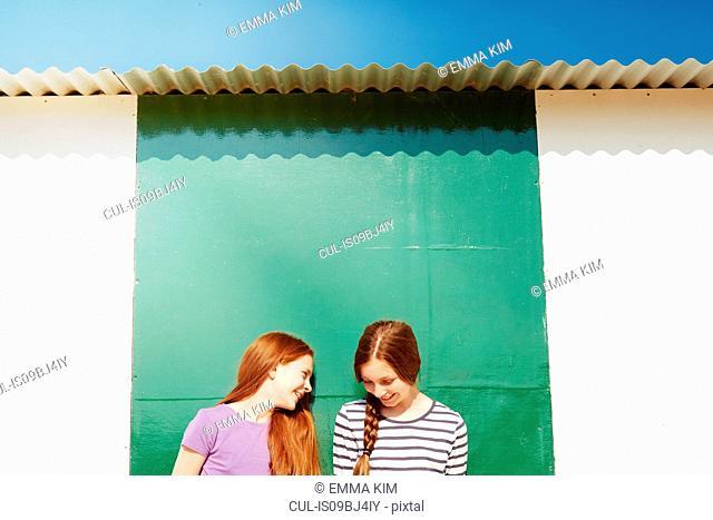 Girls behind beach hut