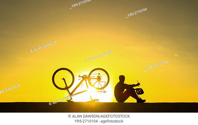 A mountain biker watches the sun rise over the Atlantic ocean from sea wall. Avenida Maritima, Las Palmas, Gran Canaria, Canary Islands, Spain. Europe