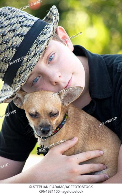 young boy holding his pet Chihuahua