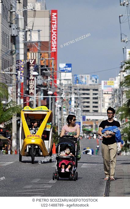 Naha (Japan): bicycle-taxi and family walking along Kokusai-dori, forbidden to cars on Sunday