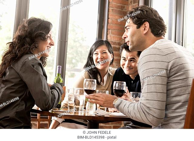 Friends drinking red wine together in restaurant