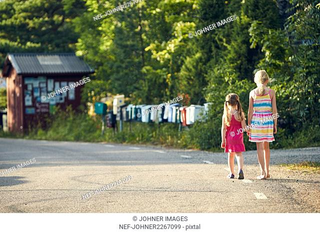 Girls holding hands while walking on road