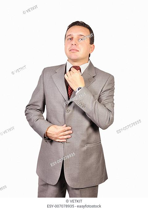 businessman adjusts his tie on white background