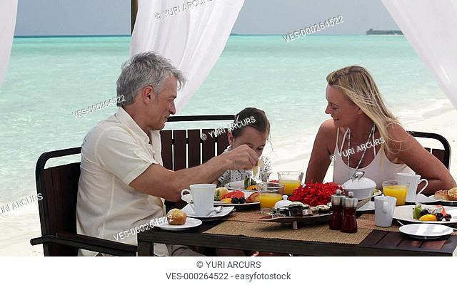 Cute little girl with her parents enjoying a beach breakfast together