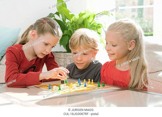 Three children playing a board game
