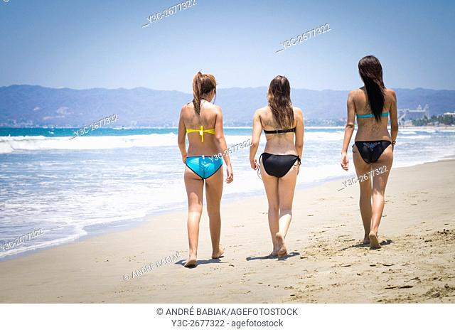 Back side of 3 young women in bikini walking at a Riviera Nayarit beach, Mexico