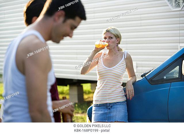 Woman leaning against van drinking an orange soda, watching two men talking in foreground