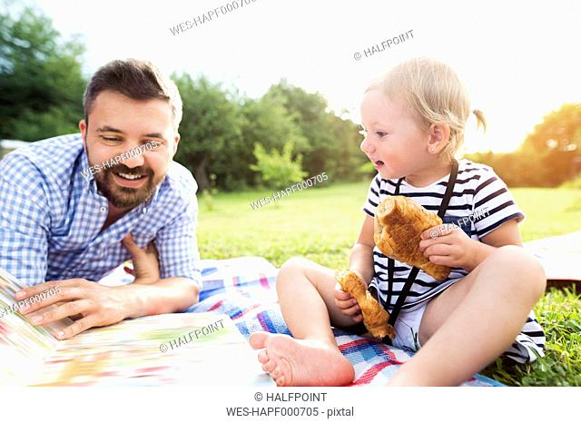 Father and his little daughter watching picture in a park