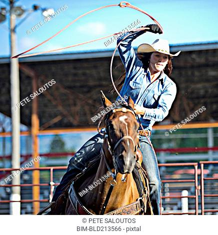 Caucasian cowgirl on horse throwing lasso in rodeo on ranch