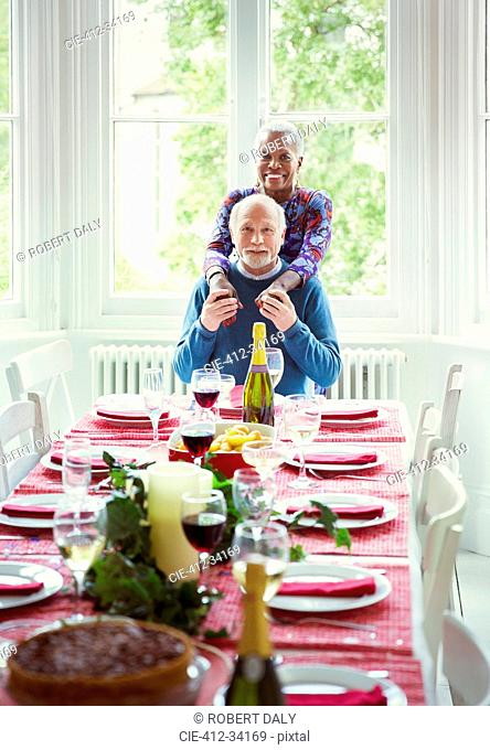 Portrait smiling multi-ethnic senior couple at Christmas dinner table