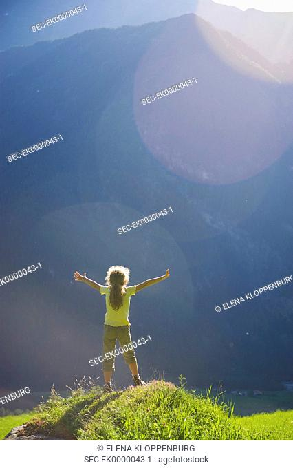 Austria, Umhausen, Girl (10-12) standing on mountaintop