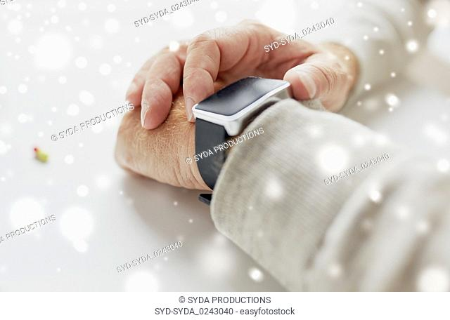close up of old man hand with pill and smart watch