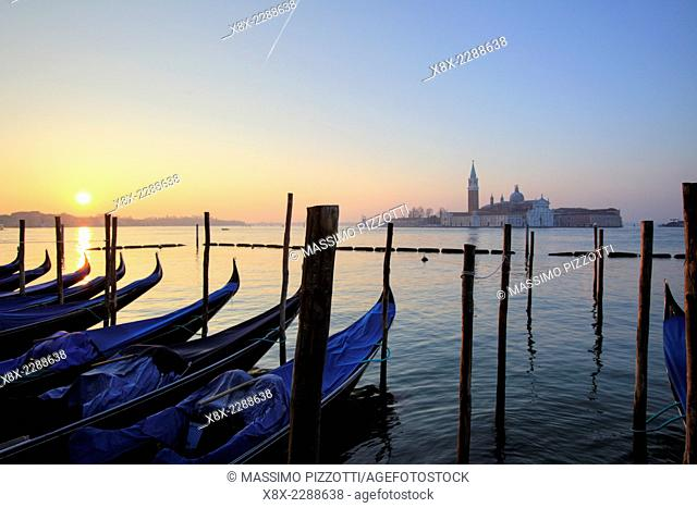 Gondolas in St. Mark's square with Saint George's island at sunrise, Venice, Italy