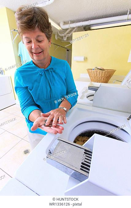 Senior woman counting change for a commercial washing machine in a laundry room