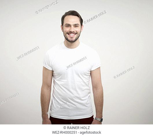 Portrait of young man standing against white background, smiling