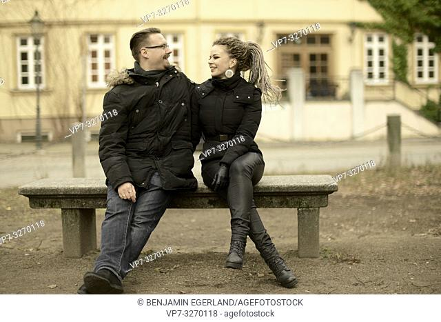 couple sitting together on stone bench in small town, in Cottbus, Brandenburg, Germany