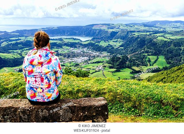 Azores, Sao Miguel, Woman sitting on stone bench looking towards the city and lake Furnas