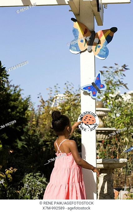 A little black girl inspects the 'Pesticide Free' ladybug sign at an organic native plant garden in California