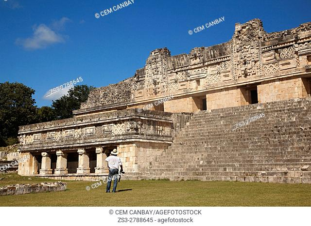 Tourist walking in Uxmal ruins near the Quadrangle Of The Nuns, in Prehispanic Mayan city of Uxmal Archaeological Site, Yucatan Province, Mexico
