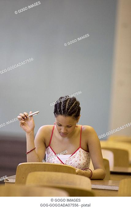 Woman studying in empty classroom