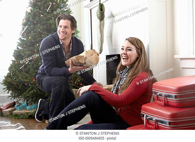 Young couple preparing log fire at christmas
