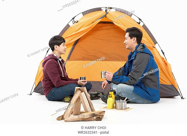 Side view of father and son camping