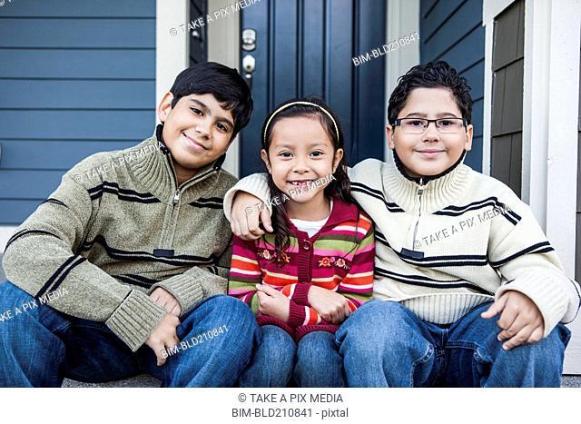Children smiling together on front stoop