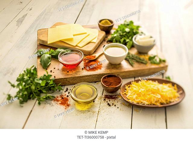 Cheese, oils and herbs on table