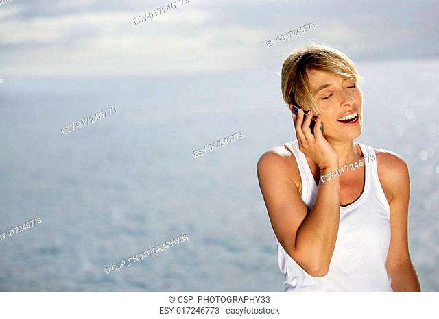 attractive blonde making a call at sunset against sea background