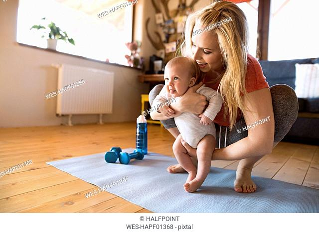 Smiling mother with baby and dumbbells at home