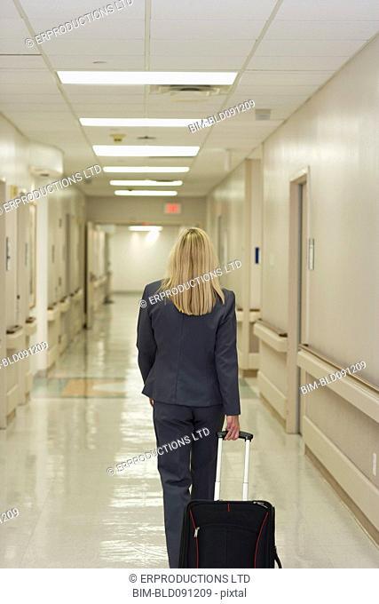 Caucasian businesswoman pulling suitcase in hospital corridor