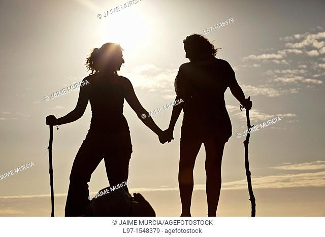 Silhouette of two girls holding hands at sunset, finisterre