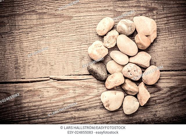 Stones on wooden background, concept of harmony and tranquility. Decoration with stone pebbles as natural design backdrop with copy space