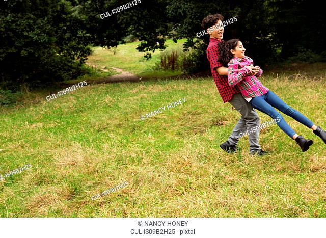 Brother and sister outdoors, fooling around, brother swinging sister around