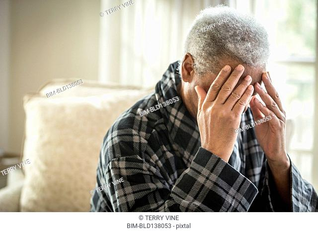 Senior African American man covering his face