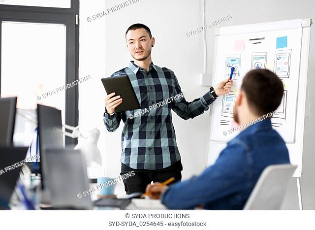 man showing tablet pc to creative team at office