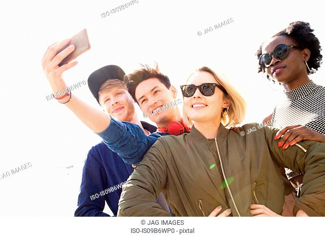 Four friends taking selfie, using smartphone, London Eye in background, London, England, UK